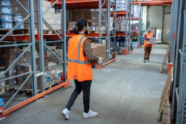 Pracownicy magazynu w kamizelkach odblaskowych przenoszą pudła podczas dystrybucji przedmiotów w magazynie z półkami z metalową ramą