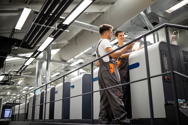 Pracownicy maszyn drukarskich kontrolujący proces drukowania i kontrolę jakości.