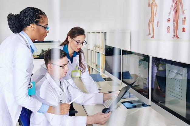 Pracownicy medyczni omawiający prześwietlenie klatki piersiowej