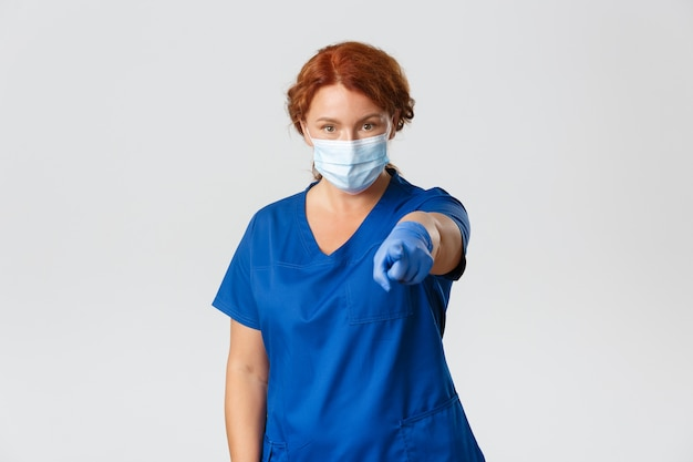 Pracownicy medyczni, pandemia covid-19, koncepcja koronawirusa. poważna i pewna siebie profesjonalna lekarka, pielęgniarka w masce i rękawiczkach wskazująca na ciebie, mówi, aby umyć ręce i zachować dystans społeczny.