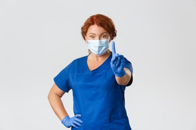 Pracownicy medyczni, pandemia, koncepcja koronawirusa. poważna profesjonalna lekarka, pielęgniarka w masce i rękawiczkach ostrzegających ludzi, potrząsając palcem w zakazie.