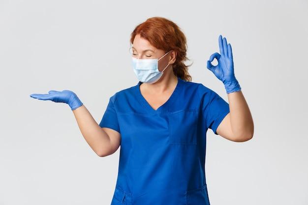 Pracownicy medyczni, pandemia, koncepcja koronawirusa. szczęśliwa uśmiechnięta lekarka, weterynarz lub lekarz w masce na twarz i rękawiczkach, trzymająca coś na dłoni i pokazująca w porządku w aprobacie, polecam