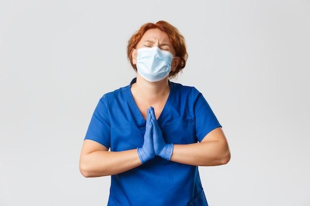 Pracownicy medyczni, pandemia, koncepcja koronawirusa. zdenerwowana błagająca ruda lekarka w masce i gumowych rękawiczkach błagająca, błagająca, wołająca o pomoc, szara ściana.