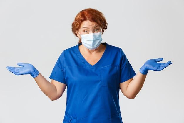 Pracownicy medyczni, pandemia, koncepcja koronawirusa. zdezorientowana i nieświadoma rudowłosa lekarka w średnim wieku, nieświadoma pielęgniarka, wzrusza ramionami i rozkłada ręce na boki, nosi maskę i rękawiczki.