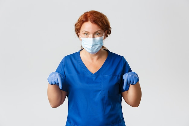 Pracownicy medyczni, pandemia, koncepcja koronawirusa. zszokowana i podekscytowana rudowłosa lekarka w średnim wieku, lekarz wskazujący palcami w dół, przekazuje ważne wiadomości i wygląda na zdumionego, szara ściana