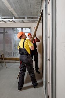 Pracownicy mocują płytę gipsowo-kartonową do ściany