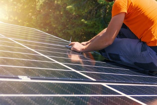 Pracownicy montują system energetyczny z panelem słonecznym do prądu i ciepłej wody