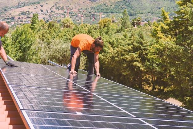 Pracownicy montują system energetyczny z panelem słonecznym na energię elektryczną