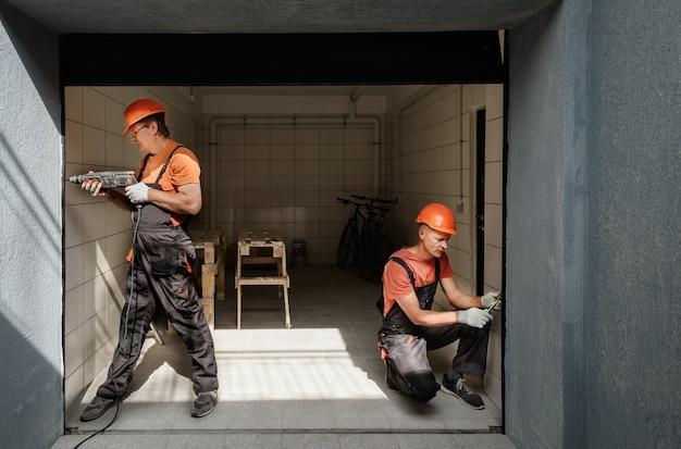 Pracownicy montują windę w garażu.