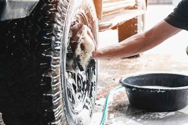 Pracownicy myjni używają gąbki zwilżonej mydłem i wodą do czyszczenia kół samochodu.