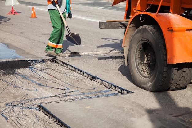 Pracownicy na maszynie do asfaltowania podczas remontu ulic drogowych