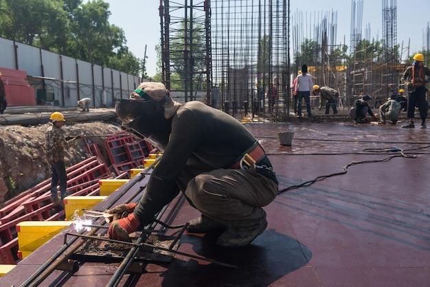 Pracownicy na placu budowy wykonują prace spawalnicze, aby wypełnić fundament betonem
