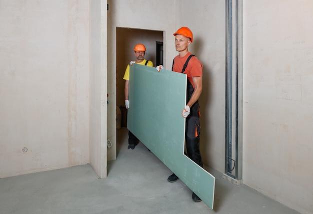 Pracownicy niosą płyty gipsowo-kartonowe do dalszego mocowania do sufitu