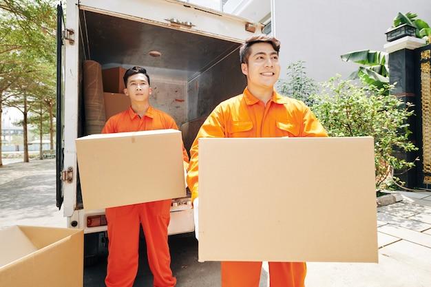 Pracownicy niosący kartony