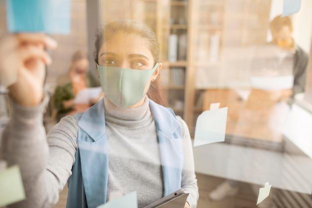 Pracownicy noszący maski na twarz w biurze