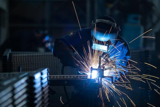 Pracownicy noszący przemysłowe mundury i spawane żelazne maski w stalowych zakładach spawalniczych.