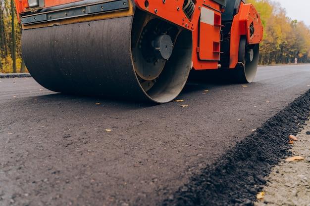 Pracownicy obsługujący asfaltową brukarz maszynę podczas budowy drogi. zamknij widok na walec drogowy pracujący na nowym placu budowy.