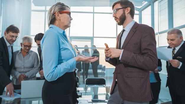 Pracownicy omawiają kwestie związane z pracą przed rozpoczęciem spotkania biznesowego. dni robocze w biurze