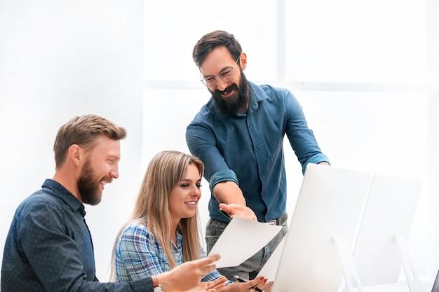 Pracownicy omawiający dokumenty biznesowe na biurku. pojęcie pracy zespołowej