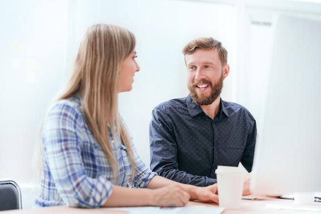 Pracownicy omawiający nowe pomysły siedząc przy biurku.