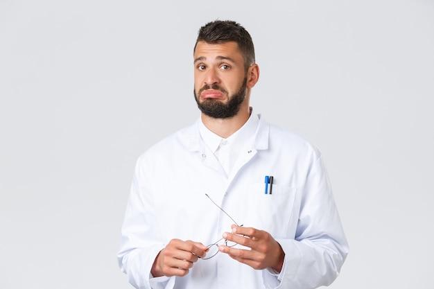 Pracownicy opieki zdrowotnej, koronawirus, pandemia covid-19 i koncepcja ubezpieczenia. przystojny niepewny lekarz w białym fartuchu medycznym, trzymający okulary, dąsający się niezdecydowany, słuchający ciekawego punktu widzenia.