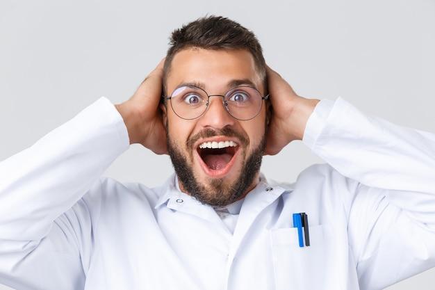 Pracownicy opieki zdrowotnej, koronawirus, pandemia covid-19 i koncepcja ubezpieczenia. zbliżenie podekscytowanego, szczęśliwego lekarza w białym fartuchu, okularach, nie mogę uwierzyć własnym oczom, trzymając ręce na głowie ze zdziwieniem