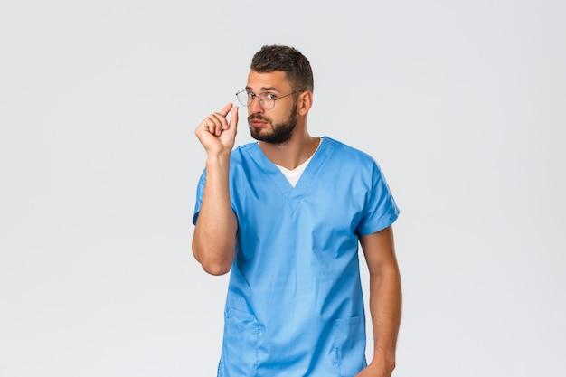 Pracownicy opieki zdrowotnej, medycyna, covid-19 i pandemiczna koncepcja samokwarantanny. lekarz wyjaśnia receptę, pokazując coś małego lub małego. pielęgniarka w zaroślach robi mały znak, szare tło