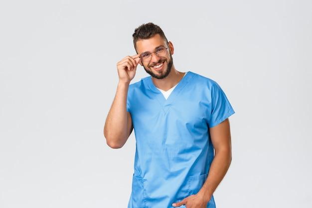 Pracownicy opieki zdrowotnej, medycyna, covid-19 i pandemiczna koncepcja samokwarantanny. przystojny wesoły mężczyzna lekarz, pielęgniarka w niebieskich fartuchach i okularach, uśmiechający się przyjazny i szczęśliwy aparat fotograficzny