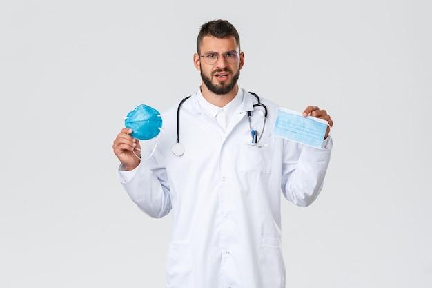 Pracownicy opieki zdrowotnej, ubezpieczenie medyczne, koncepcja pandemii i covid-19. zakłopotany młody przystojny lekarz w białym fartuchu, okularach pokazujących respirator i maskę medyczną, dwa różne środki ochrony osobistej.
