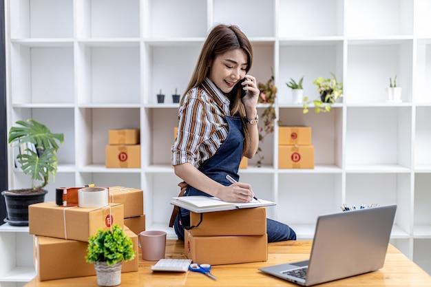 Pracownicy piszą przesyłki klientów, aby zamawiać produkty za pośrednictwem witryn internetowych i dostarczać produkty za pośrednictwem prywatnych usług transportowych. koncepcje sprzedaży produktów online. miejsce na kopię.