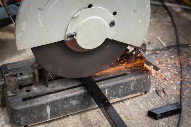 Pracownicy płci męskiej tną i spawają metal za pomocą iskry.