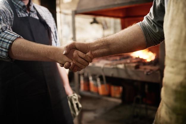 Pracownicy podają sobie ręce podczas pracy