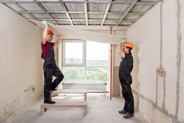 Pracownicy podnoszą płyty gipsowo-kartonowe, aby przymocować je do sufitu