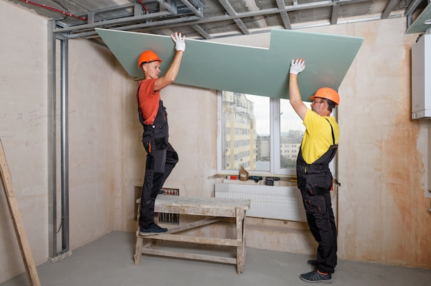 Pracownicy podnoszą płyty gipsowo-kartonowe w celu ich dalszego przymocowania do sufitu