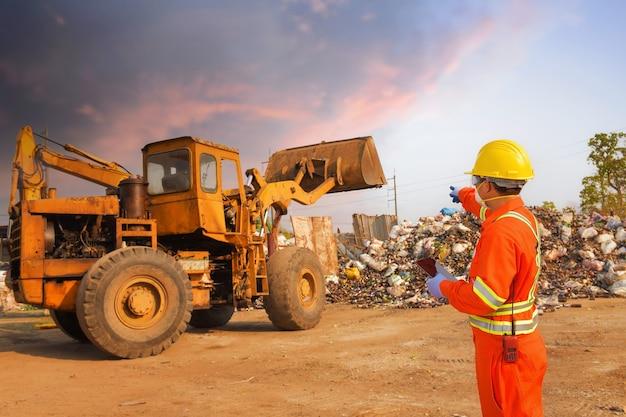 Pracownicy portretowi ubrani w kombinezony i kaski chroniące przed zagrożeniem biologicznym pracujący w sortowni odpadów w fabryce