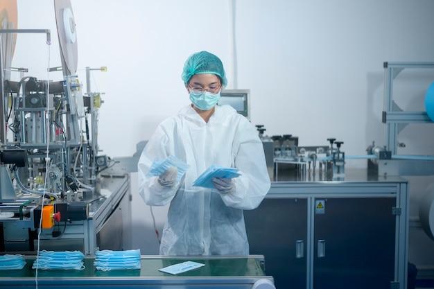 Pracownicy produkujący maskę chirurgiczną w nowoczesnej fabryce, ochrona covid-19 i koncepcja medyczna.