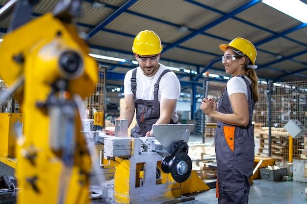 Pracownicy przemysłowi pracujący razem na linii produkcyjnej fabryki