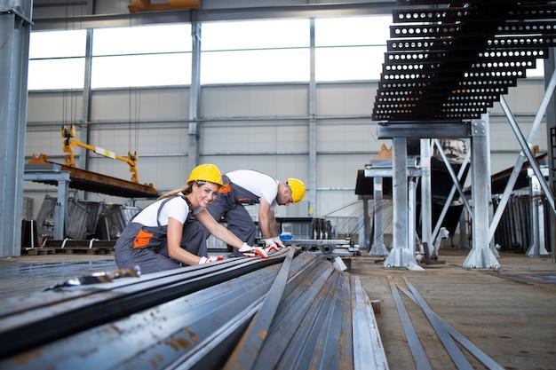 Pracownicy przemysłowi pracujący w hali fabrycznej z metalem.