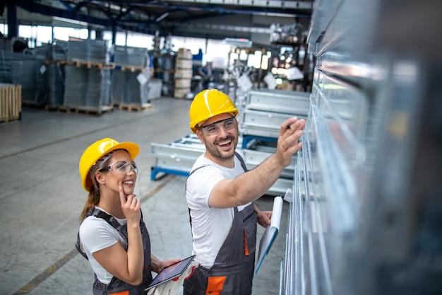Pracownicy przemysłowi sprawdzający jakość wyrobów metalowych w zakładzie produkcyjnym.