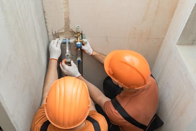Pracownicy przylutowują kran ścienny do wbudowanego prysznica