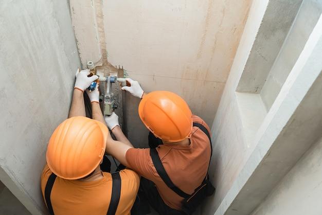 Pracownicy przylutują kran ścienny do wbudowanego prysznica
