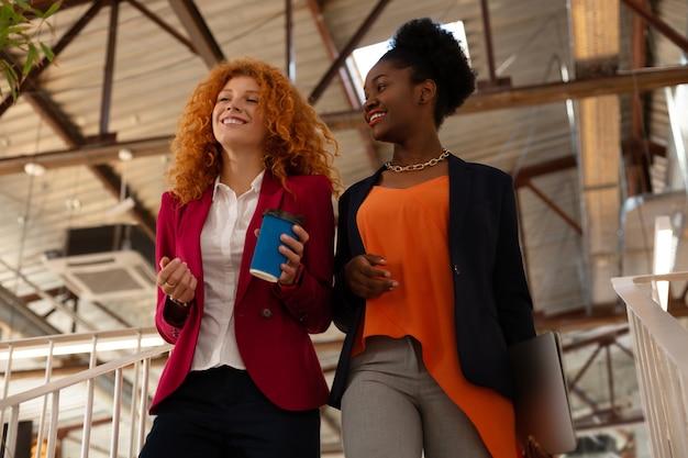 Pracownicy rozmawiają. dwóch pięknych stylowych pracowników chodzących po biurze i rozmawiających