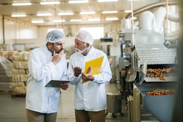 Pracownicy rozmawiają o jakości żywności. w ręce wykres i tablet.