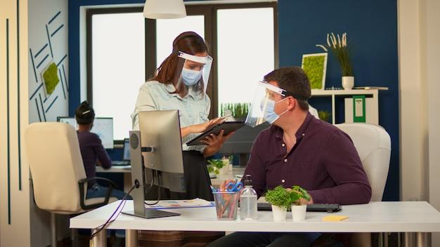 Pracownicy rozmawiają o pisaniu projektów na komputerze i tablecie, nosząc maski ochronne w pokoju biurowym podczas koronawirusa. wieloetniczny zespół pracujący w firmie z nową normalną respektującą dystans społeczny.