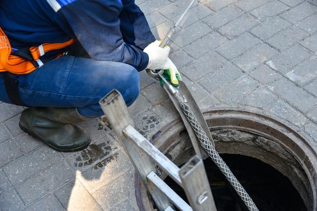 Pracownicy rozmontowują kabel telekomunikacyjny w studni