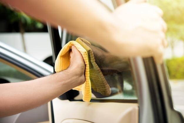 Pracownicy serwisu samochodowego czyszczący szybę samochodu