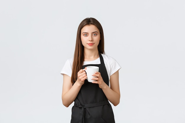 Pracownicy sklepu spożywczego, koncepcja małych firm i kawiarni. ładny żeński barista w czarnym fartuchu po przerwie, pije z kubka