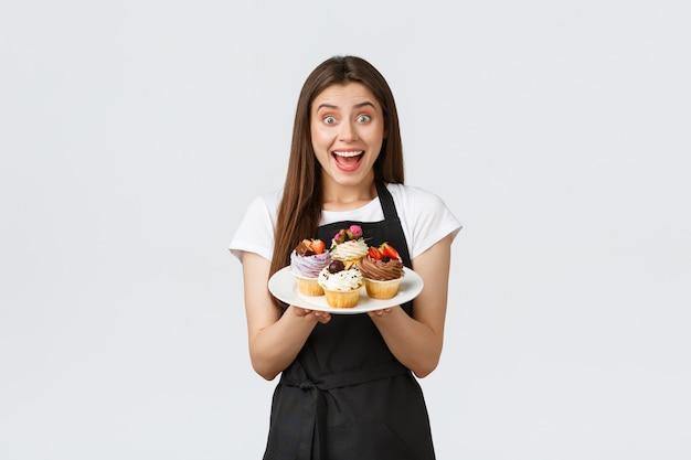 Pracownicy sklepu spożywczego, koncepcja małych firm i kawiarni. podekscytowana kobieta barista, kawiarnia pracująca w czarnym fartuchu trzymająca talerz z babeczkami, pokazująca nowe menu letnie desery w kawiarni