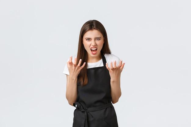 Pracownicy sklepu spożywczego, koncepcja małych firm i kawiarni. szalona sprzedawczyni skarży się na niegrzecznych klientów, zaciska ręce gniewnie i krzywi się gniewnie, stojąc na białym tle.