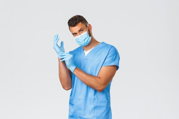 Pracownicy służby zdrowia, covid-19, koronawirus i koncepcja zapobiegania wirusowi. przystojny młody profesjonalny lekarz, pielęgniarz w masce medycznej i peelingach, zakłada gumowe rękawiczki, aby obserwować pacjenta